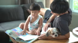 Father with a toddler boy and dog relaxing in a living room at home.