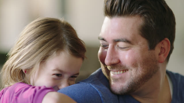 CU. Father with acoustic guitar kisses his daughter on the nose as she leans on his shoulder.