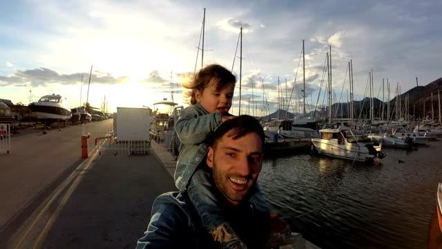 ボートの上を歩く女の赤ちゃんを持つ父ドックします。