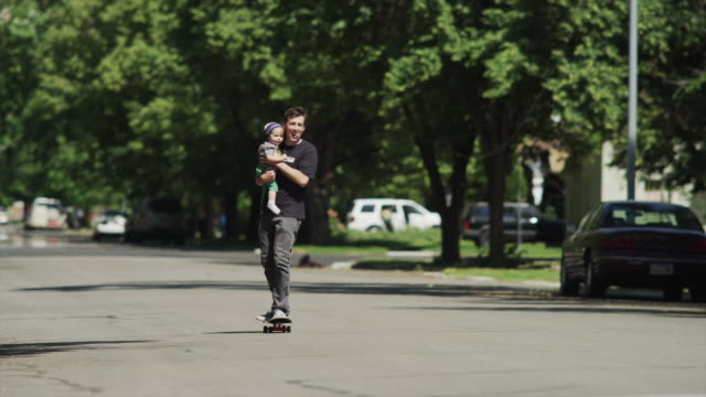 slo mo ws father with baby son (12-17 months) skateboarding / provo, utah, usa - provo stock videos & royalty-free footage