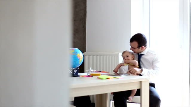 Father With Baby Working In Office At Home