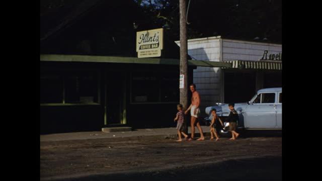 1952 ws pan father with boys, all barefoot outside hunt's coffee bar / grand bend, ontario, canada - 1952 bildbanksvideor och videomaterial från bakom kulisserna