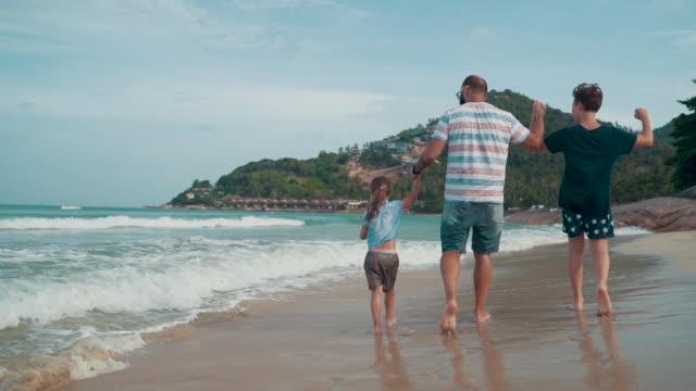 vídeos de stock e filmes b-roll de father with children enjoy walking on the beach - irmão