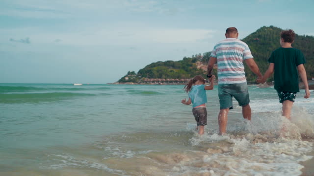 father with children enjoy walking on the beach - single father stock videos & royalty-free footage