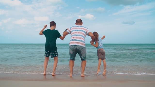 Pappa med barn som leker på stranden