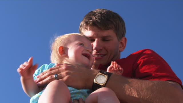 slo mo cu la father with daughter (6-11 months) against clear sky / utah, usa - augen zuhalten stock-videos und b-roll-filmmaterial