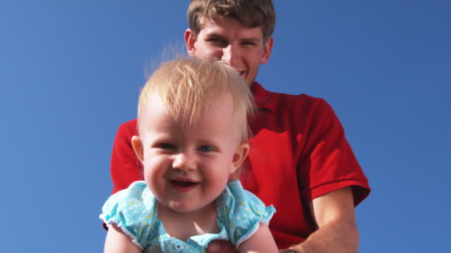 stockvideo's en b-roll-footage met slo mo cu la father with daughter (6-11 months) against clear sky / utah, usa - 6 11 maanden