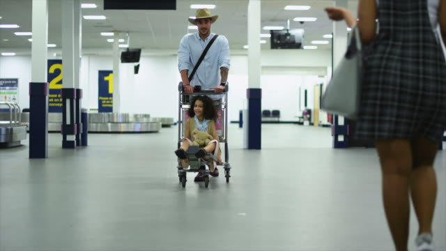 father with daughter and women walking at airport - wheeled luggage stock videos and b-roll footage