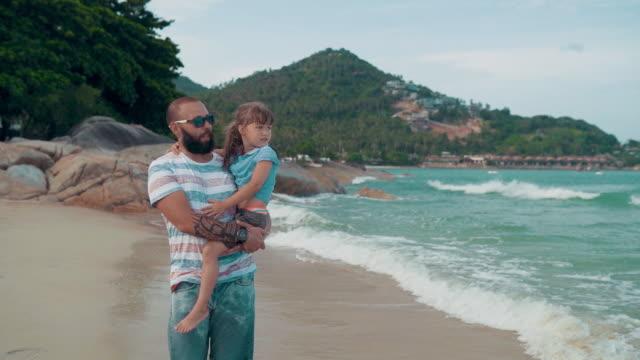 Far med dotter njuta av promenader på stranden