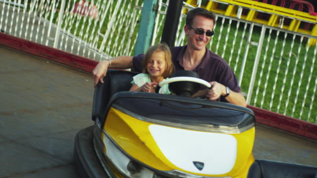 ms father with daughter (6-9) in bumper-car at amusement park / rutland, vermont, usa - バーモント州点の映像素材/bロール