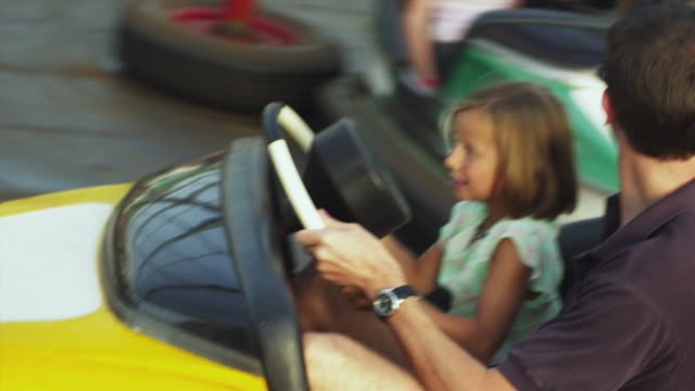 ms pan father with daughter (6-7) in bumper-car at amusement park / rutland, vermont, usa - bumper car stock videos & royalty-free footage