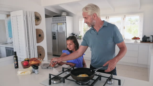 father with daughter in kitchen - salt shaker stock videos and b-roll footage
