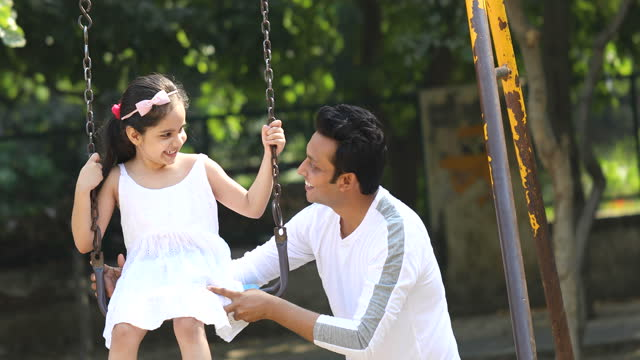 father with daughter on swing at park - swinging stock videos & royalty-free footage