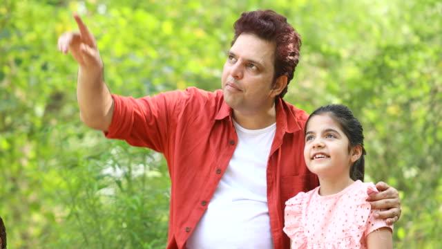 vídeos de stock e filmes b-roll de father with daughter outdoors at park - genderblend