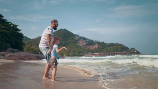 Far med dotter leker på stranden