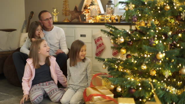 stockvideo's en b-roll-footage met father with daughters on christmas day at home - familie met drie kinderen