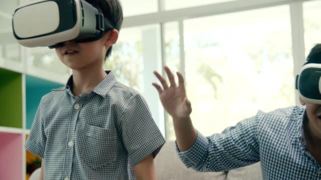自宅のリビングルームでvrメガネと一緒にビデオゲームをしている彼の息子と父親 - 大家族点の映像素材/bロール