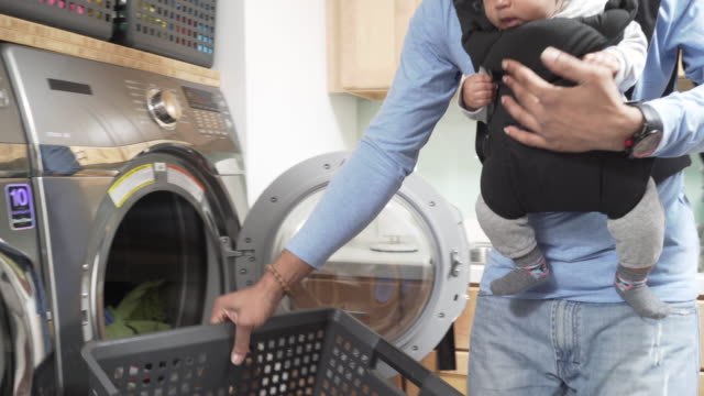 vídeos de stock, filmes e b-roll de father with infant in baby carrier doing laundry - bebês meninos