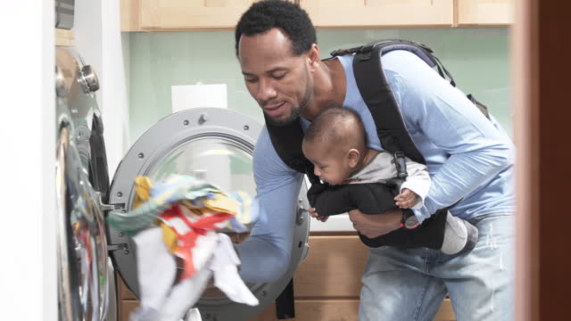 father with infant in baby carrier doing laundry - laundry stock videos & royalty-free footage