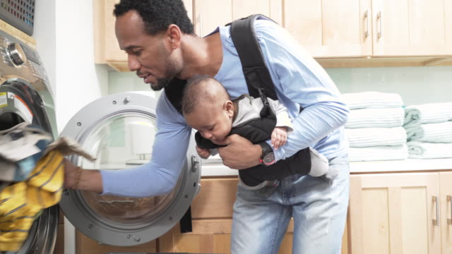 father with infant in baby carrier doing laundry - baby carrier stock videos & royalty-free footage