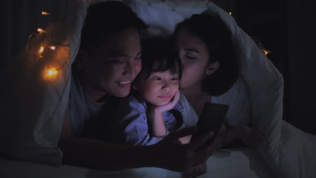 father with little children surfing on tablet computer before sleeping - film stock videos & royalty-free footage