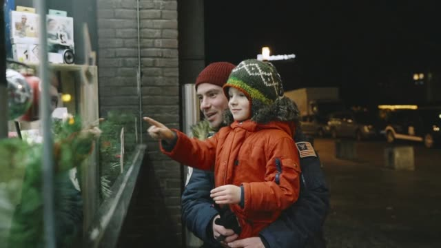 father with little son looking at  store window on christmas - window display stock videos & royalty-free footage