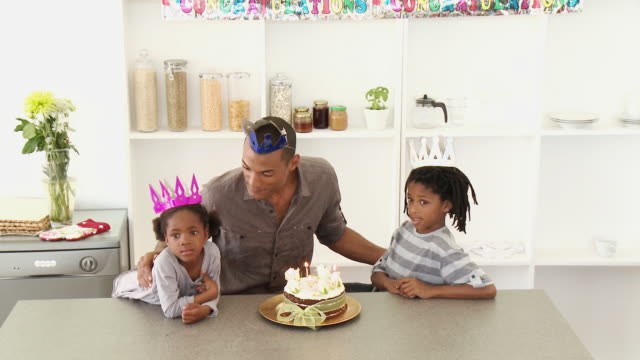 MS Father with son (8-9) and daughter (4-5) blowing birthday candles together / Cape Town, Western Cape, South Africa