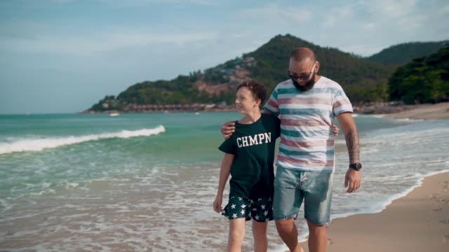 Far med son njuta av promenader på stranden
