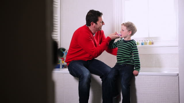 father with son in bathroom - toothbrush stock videos & royalty-free footage