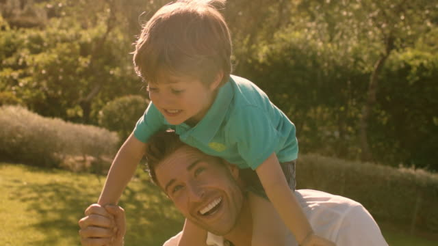 father with son on shoulders in park. - ridere video stock e b–roll