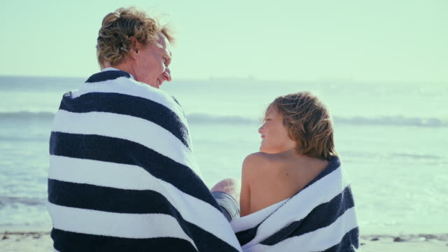 father with son sitting on beach - wrapped in a towel stock videos and b-roll footage
