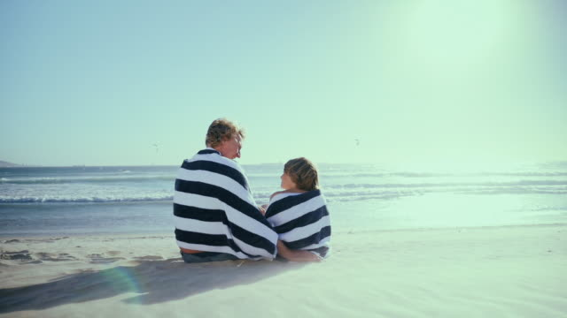 father with son sitting on beach - towel stock videos & royalty-free footage