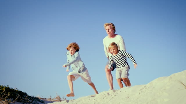 father with sons jumping on beach - family with two children stock videos & royalty-free footage