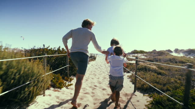 father with sons running on beach - beach holiday stock videos & royalty-free footage