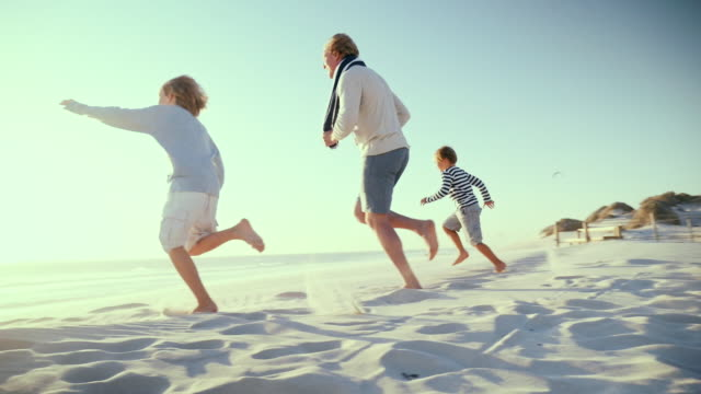 vidéos et rushes de father with sons running on beach - 45 49 ans