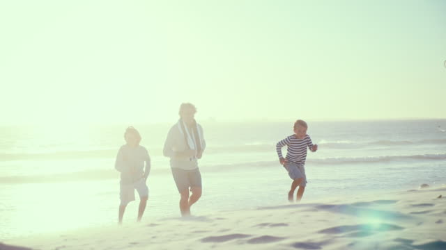 Father with sons running on beach