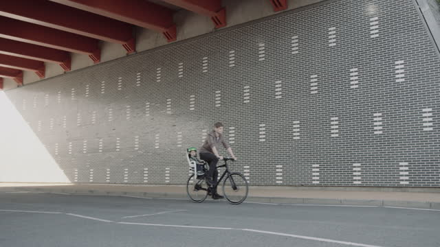 father with toddler in bicycle seat cycling on urban road in city - bicycle seat stock videos & royalty-free footage