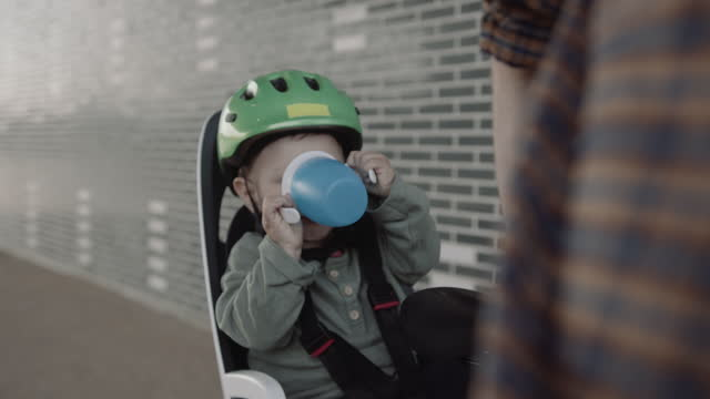 father with toddler in bicycle seat urban road in city drinking water from cup - bicycle seat stock videos & royalty-free footage