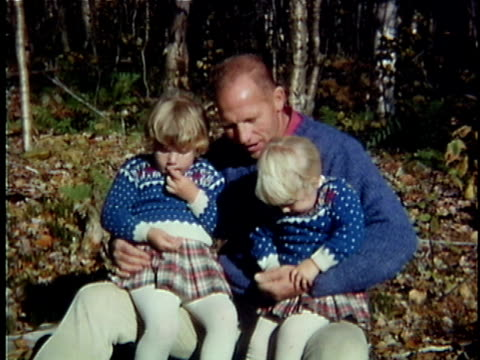 1963 MS Father with two daughters on laps in forest, Vermont, USA