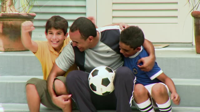 vídeos y material grabado en eventos de stock de ms father with two sons (9-12) sitting together holding soccer ball and laughing, panama city, panama  - américa central
