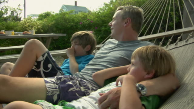 CU, Father with two sons (8-9, 10-11) swinging on hammock, Truro, Cape Cod, Massachusetts, USA