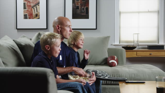 ms zi father with two sons (8-11) watching match on tv and eating popcorn / orem, utah, usa - son stock videos & royalty-free footage