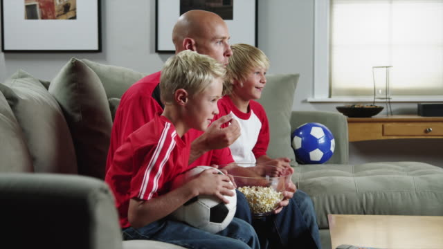MS ZI Father with two sons (8-11) watching match on TV and eating popcorn / Orem, Utah, USA