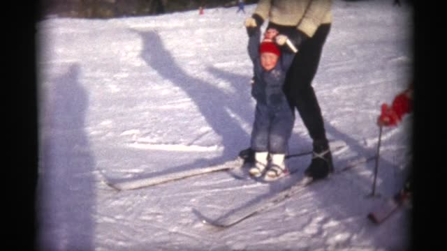 stockvideo's en b-roll-footage met 1963 father with young skier with tiny skis atop chateau-d'oex, switzerland - onderwijzen