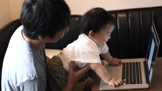 father working at home , his baby touching laptop - two generation family stock videos & royalty-free footage