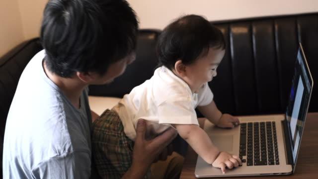 vídeos de stock, filmes e b-roll de father working at home , his baby touching laptop - família de duas gerações