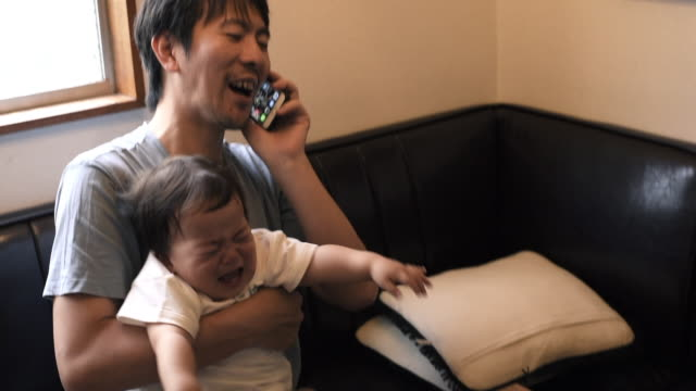 vídeos de stock e filmes b-roll de father working at home holding crying baby - um dia na vida de