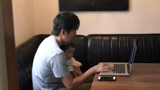 father working at home holding his baby - ライフスタイル点の映像素材/bロール