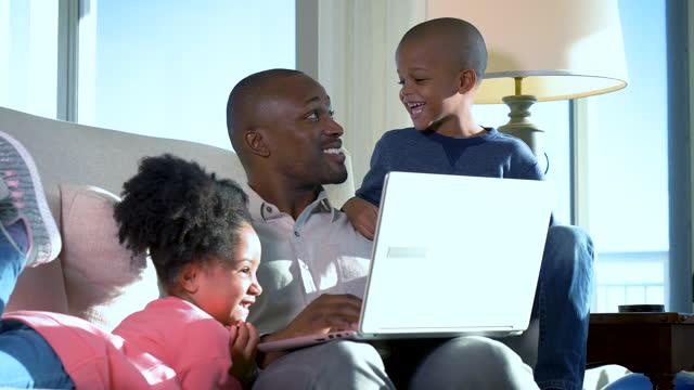 vater arbeitet zu hause am laptop, mit zwei kindern - 35 39 years stock-videos und b-roll-filmmaterial