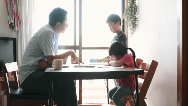 vídeos de stock, filmes e b-roll de pai trabalhando em casa com filhos - vida simples